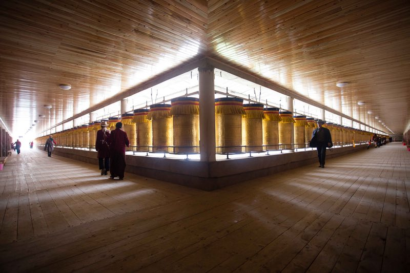 Pilgrims spin prayer wheels in the monastery above Lithang